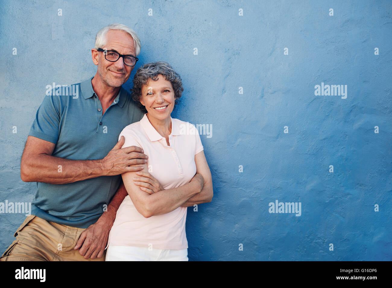 Porträt von glücklich senior Mann und Frau gemeinsam vor blauem Hintergrund. Mittleren gealterten paar Stockbild