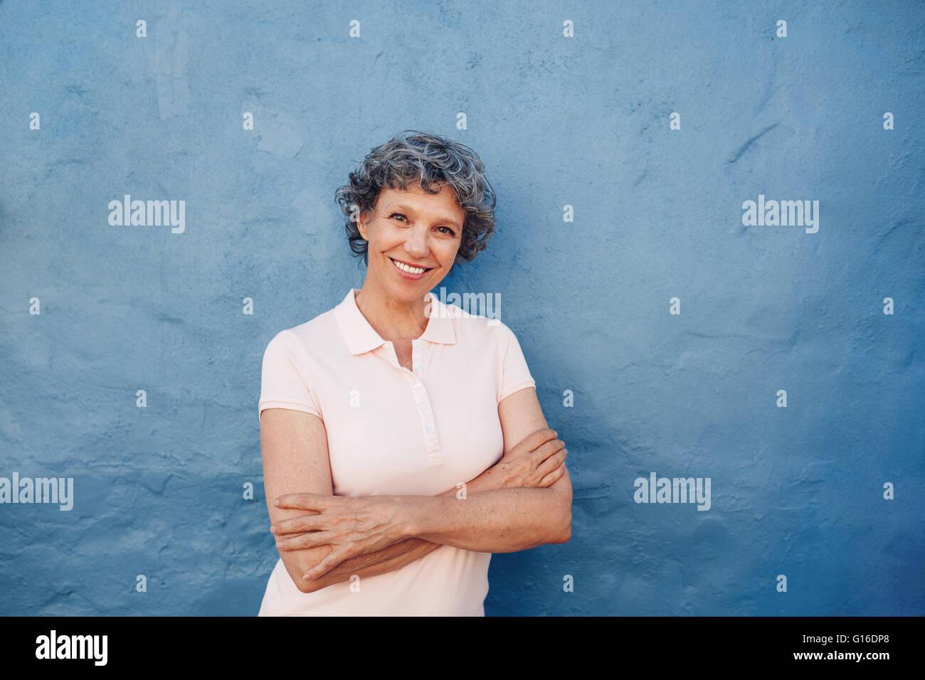Porträt von attraktive Reife Frau mit ihren Armen gekreuzt stehenden vor blauem Hintergrund. Sie lehnt an einer Stockbild
