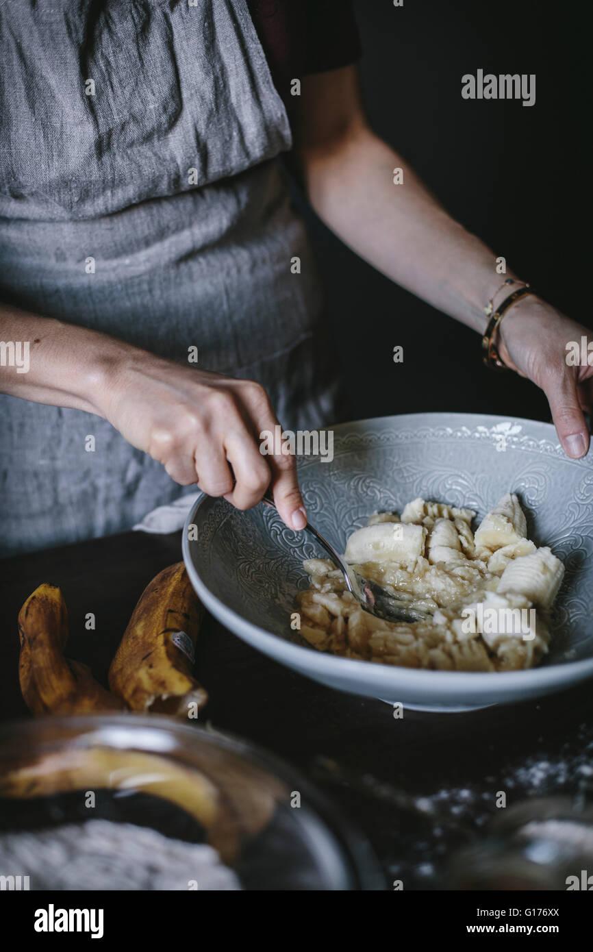 Eine Frau ist Bananen in einer Banane Brot Donut Rezept zu verwendenden Maischen. Stockbild
