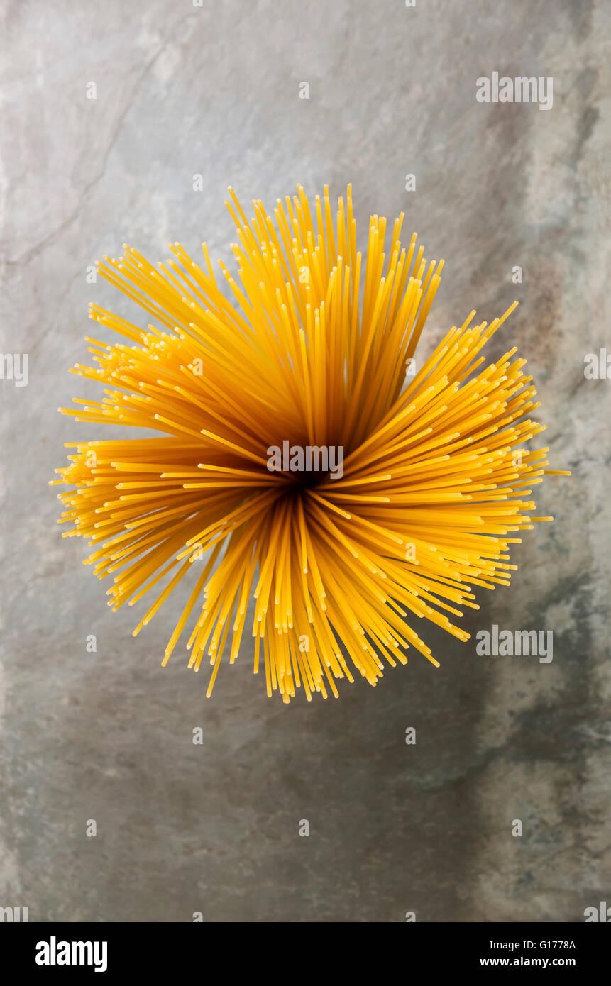Draufsicht Blütenform Bündel Spaghetti auf grauem Stein Schiefer Hintergrund Stockbild