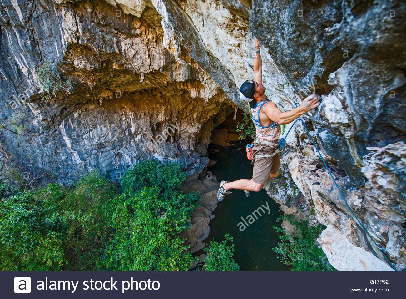Junger Mann Klettern, in der Nähe von Thakhek, Khammuan, Laos Stockbild