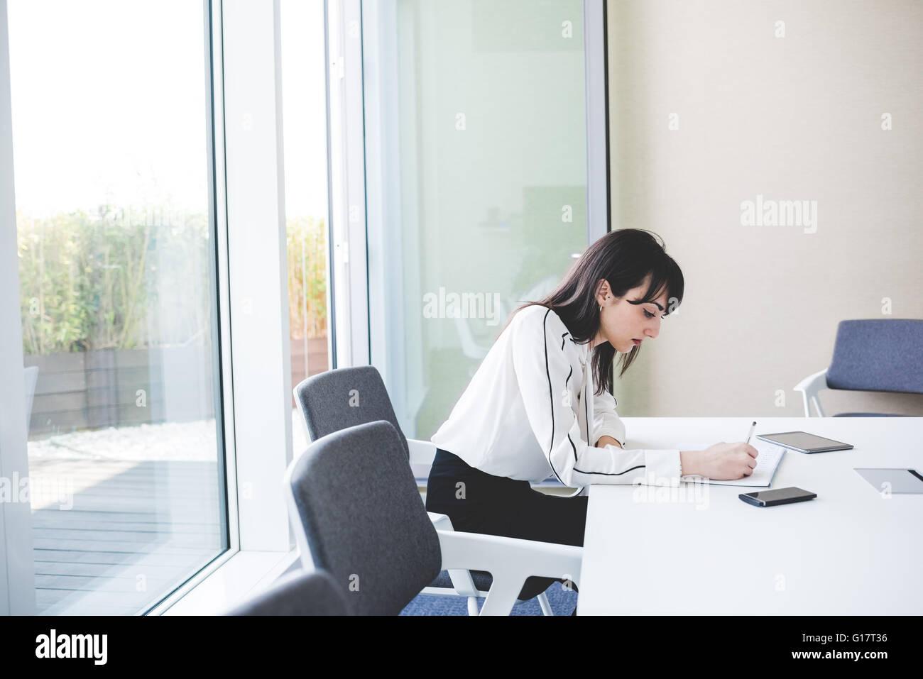Junge Geschäftsfrau Schreiben von Notizen am Schreibtisch Stockbild