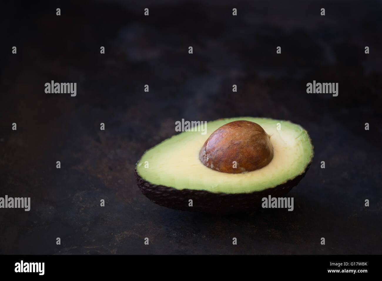 die Hälfte der eine Reife Avocado vor einem rustikalen dunklen Hintergrund Stockbild
