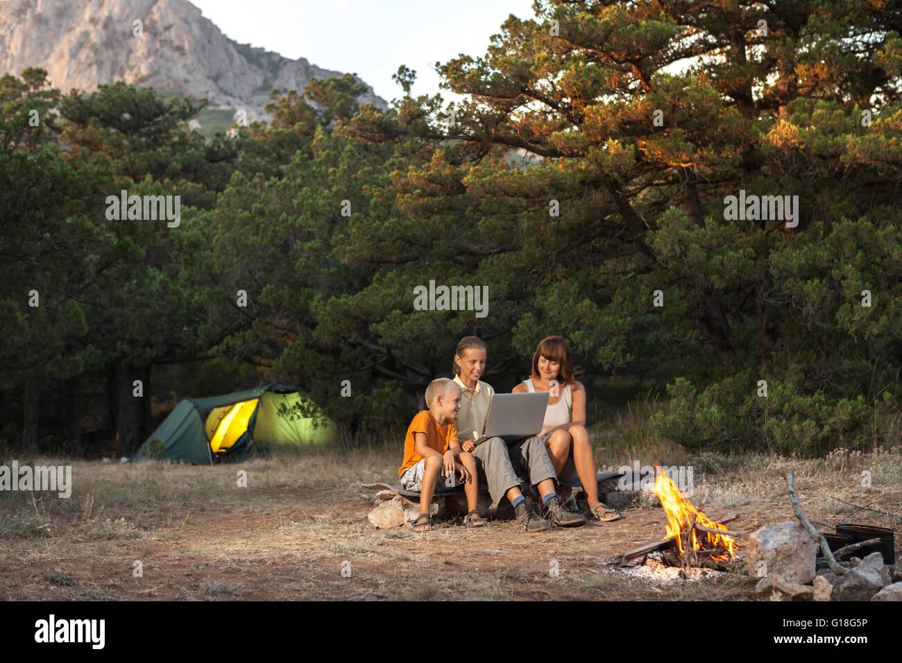 Familie von Trhee Personen mit Laptop auf dem Campingplatz Stockbild