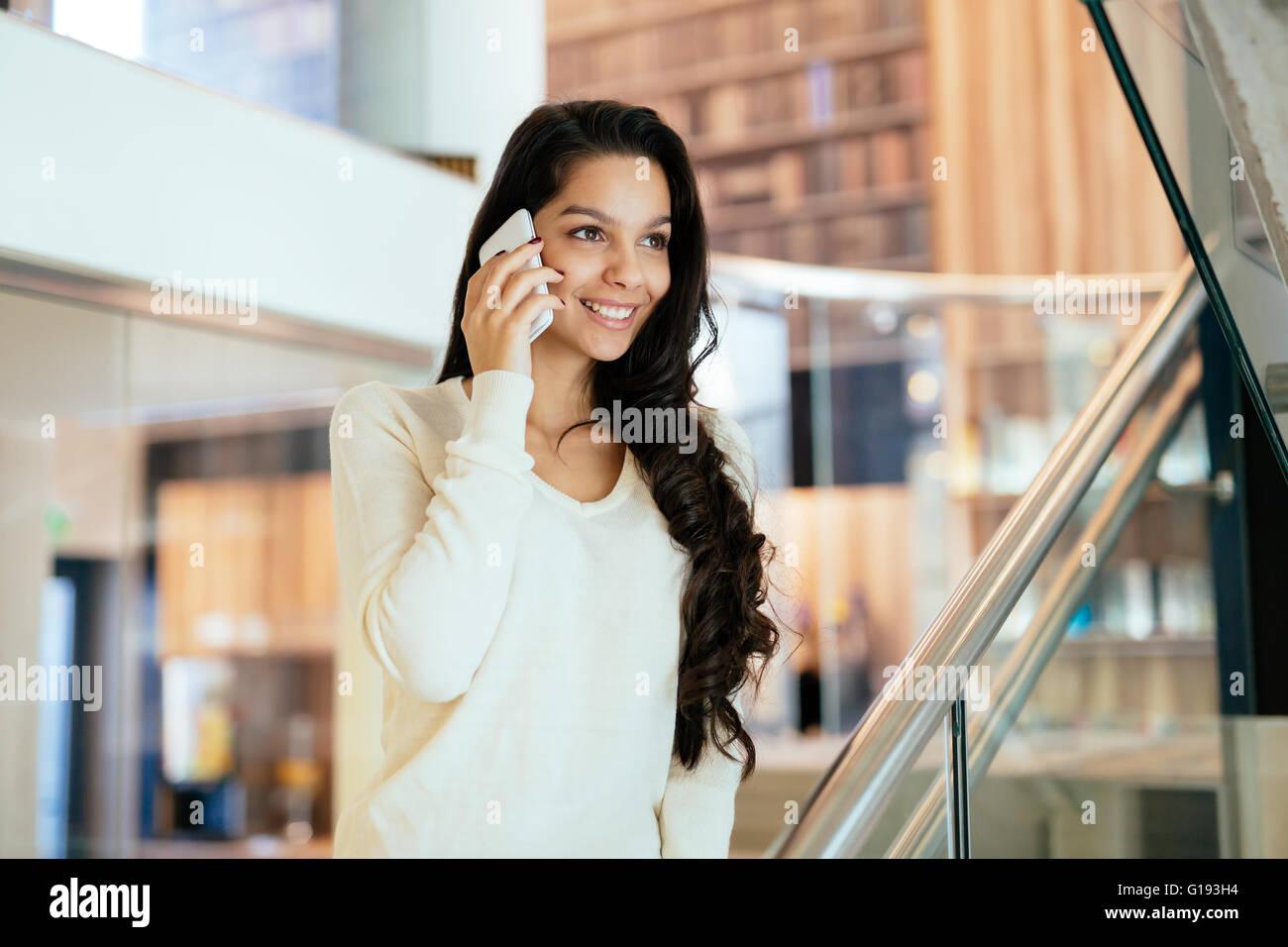 Geschäftsfrau mit Handy drinnen und lächelnd Stockbild