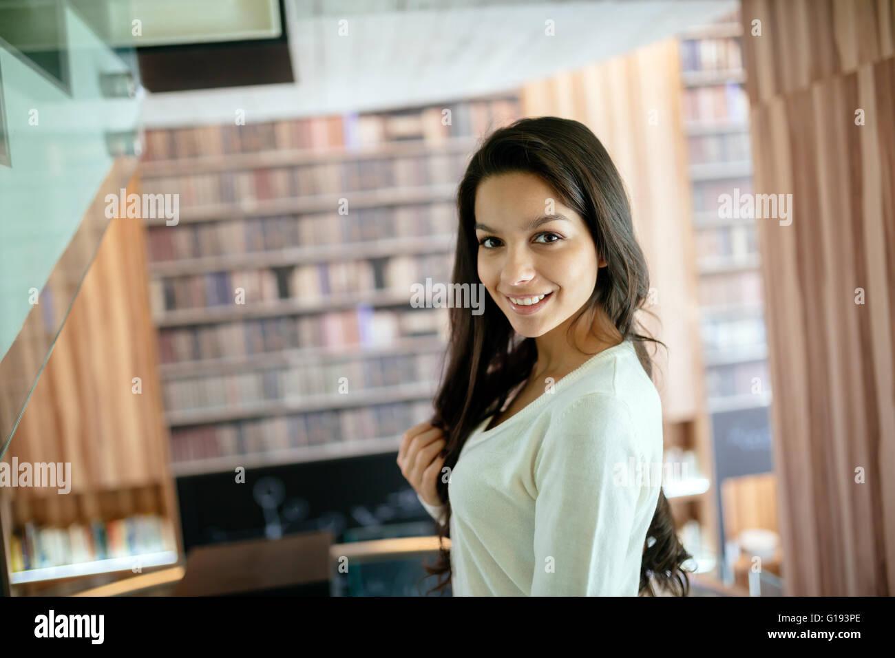 Schöne Brünette posiert in Bibliothek Stockbild