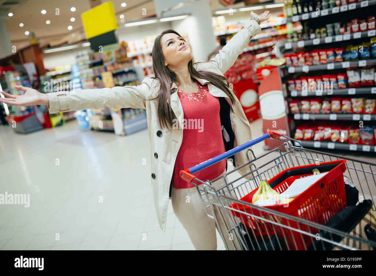 Frau glücklich beim Einkaufen im Supermarkt Stockbild