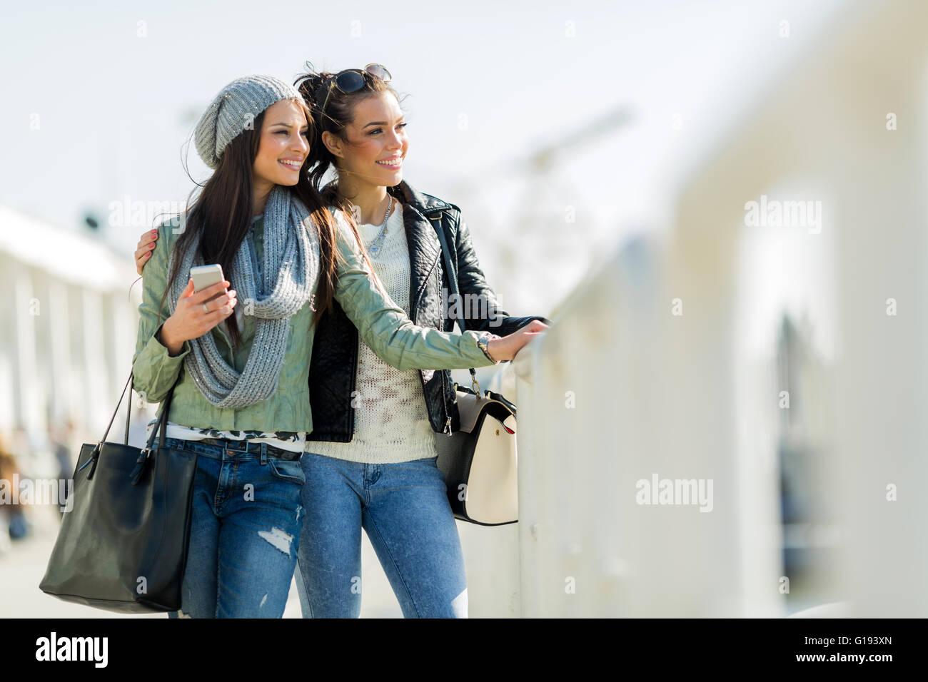 Zwei junge und schöne Frauen auf der Suche über einen Dock-Zaun Stockbild