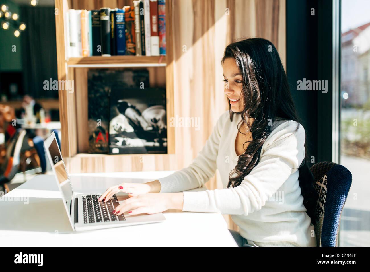 Schöne Brünette mit Laptop im café Stockbild