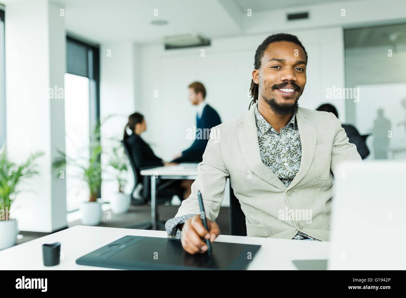 Schwarze schöne Grafik-Designer mit Dreadlocks mit Digitizer in einer gut beleuchteten, ordentlich Büroumgebung Stockbild