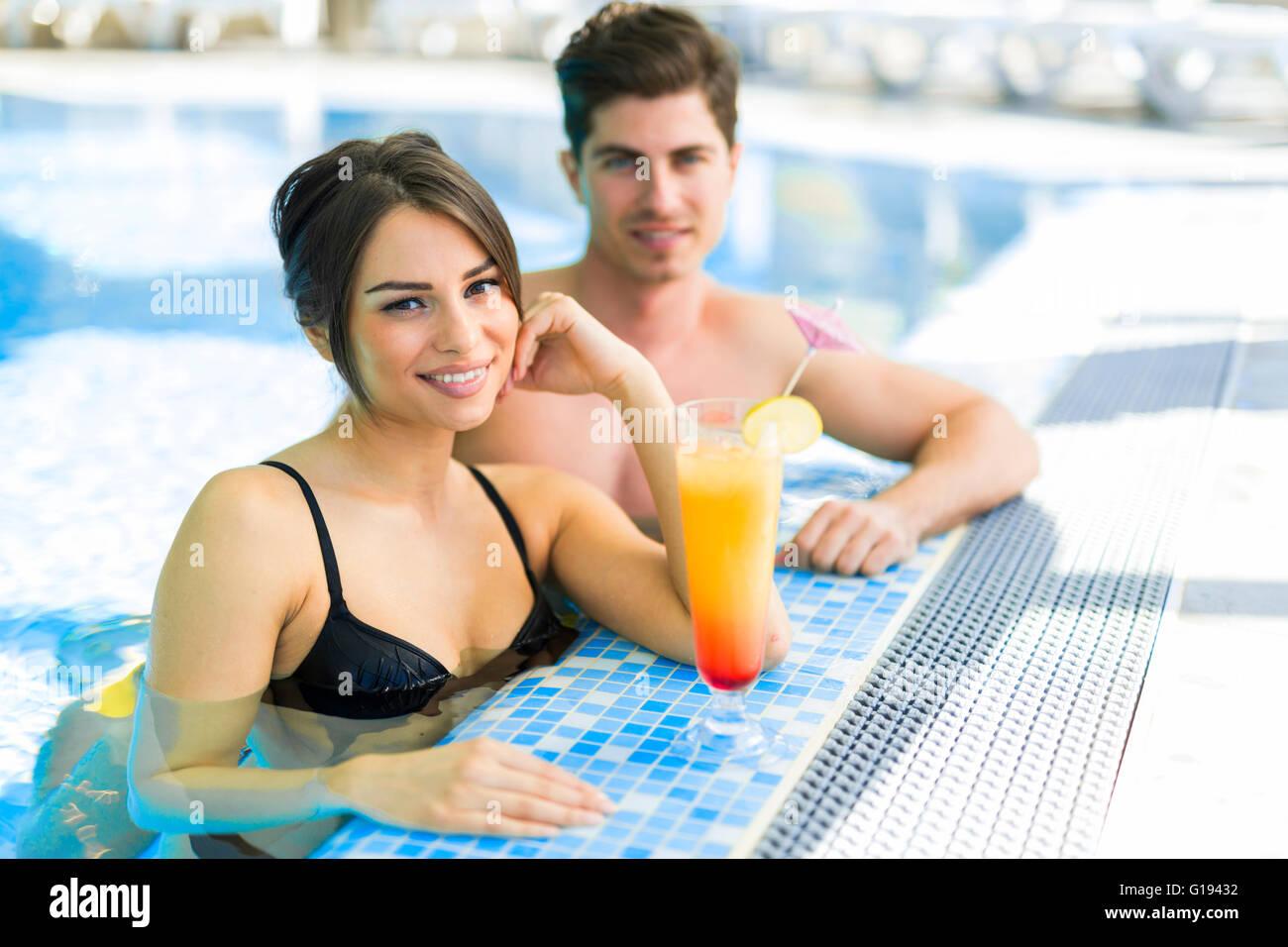 Paar, trinken einen Cocktail am Pool und entspannen Stockbild