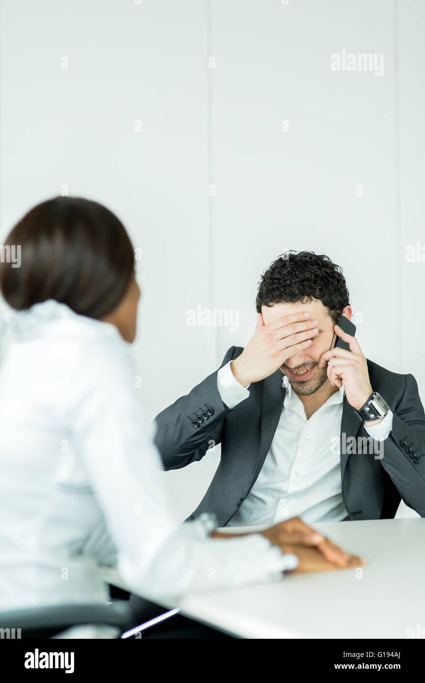 Geschäftsmann erhält schlechte Nachrichten auf dem Handy mit Kopfschmerzen über die Probleme Stockbild