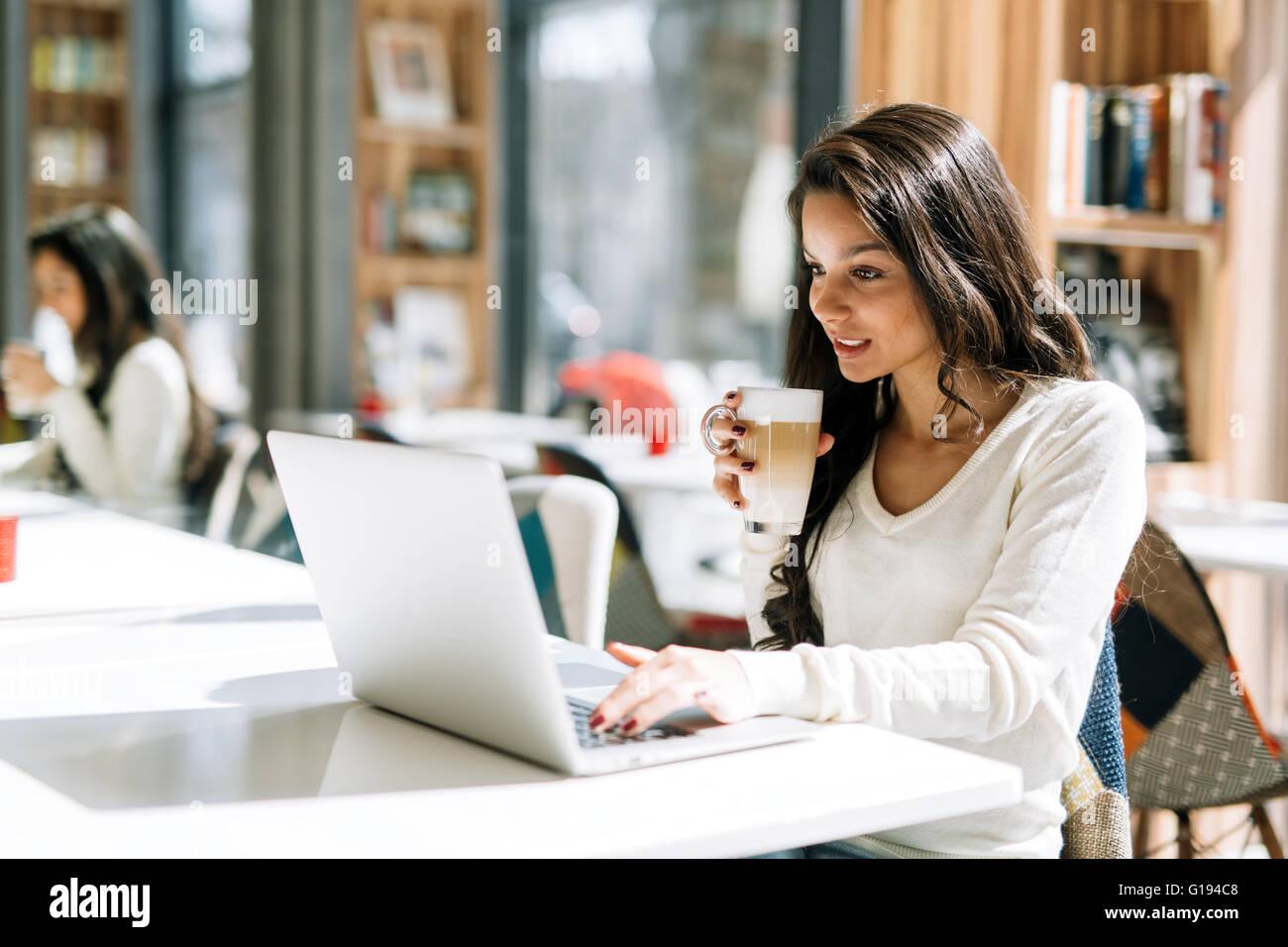 Schöne Brünette Kaffeegenuss und mit laptop Stockbild