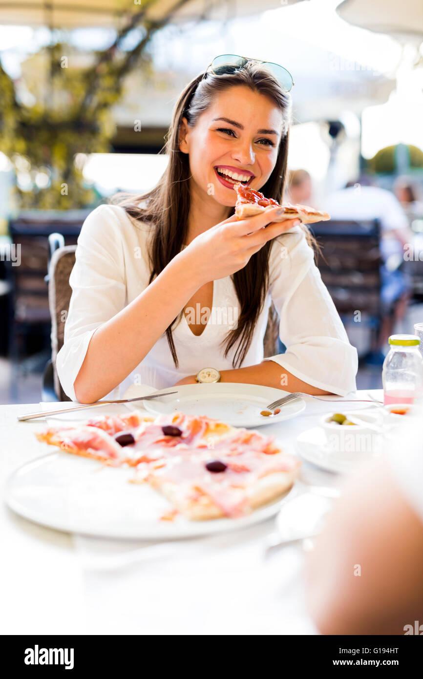 Schöne junge Frau Essen ein Stück Pizza in einem Restaurant im freien Stockbild