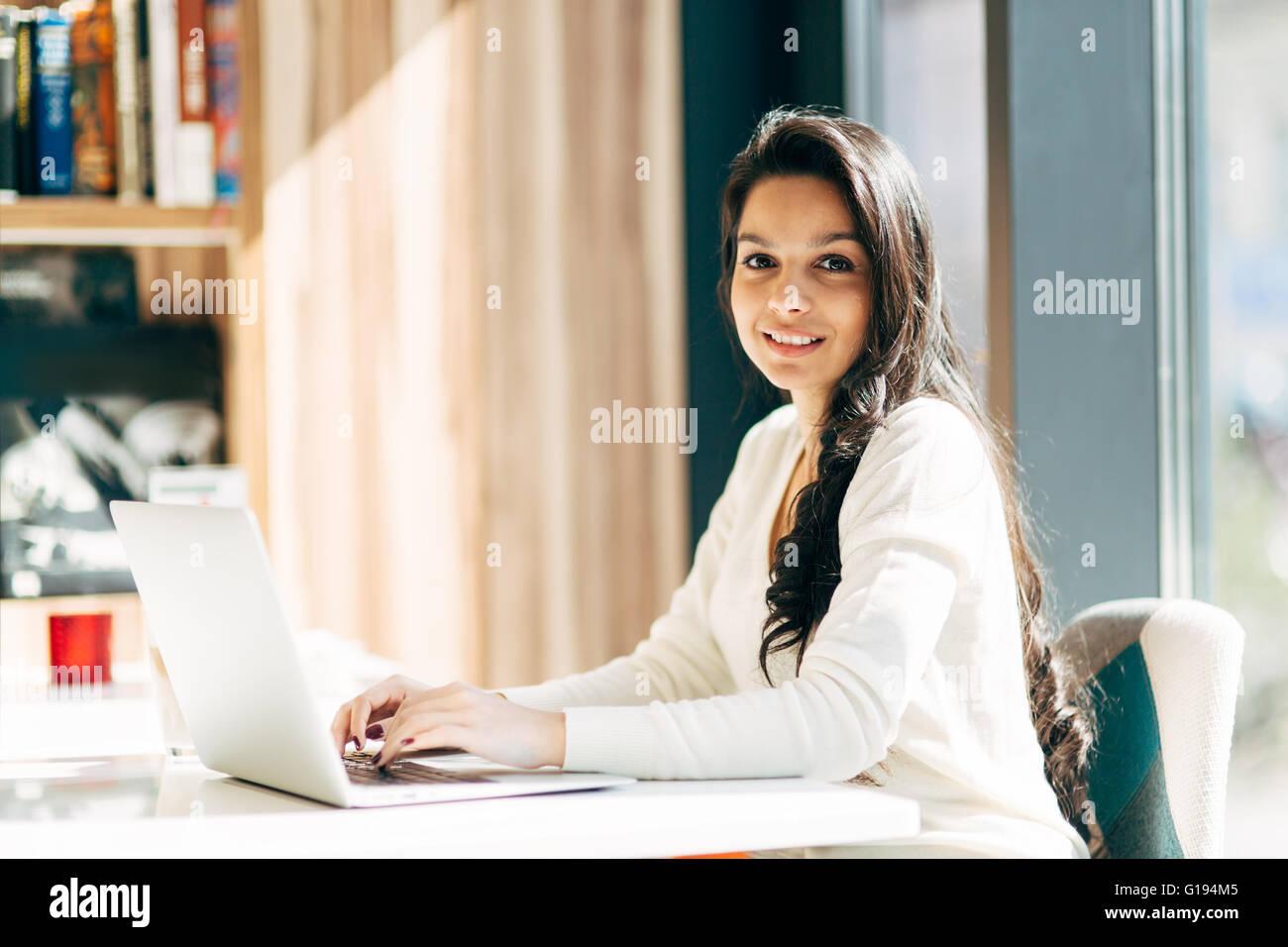 Schöne Brünette mit Notebook im café Stockbild