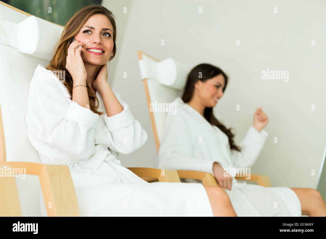Junge und schöne Frauen Entspannung in einem Spa Roben tragen und am Telefon sprechen Stockbild
