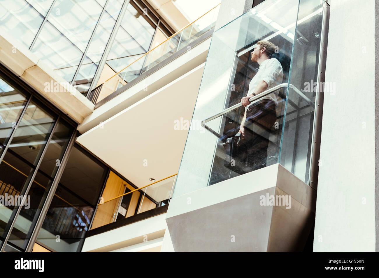 Unternehmer, die unter modernen gläsernen Aufzug zu den oberen Stockwerken Stockbild