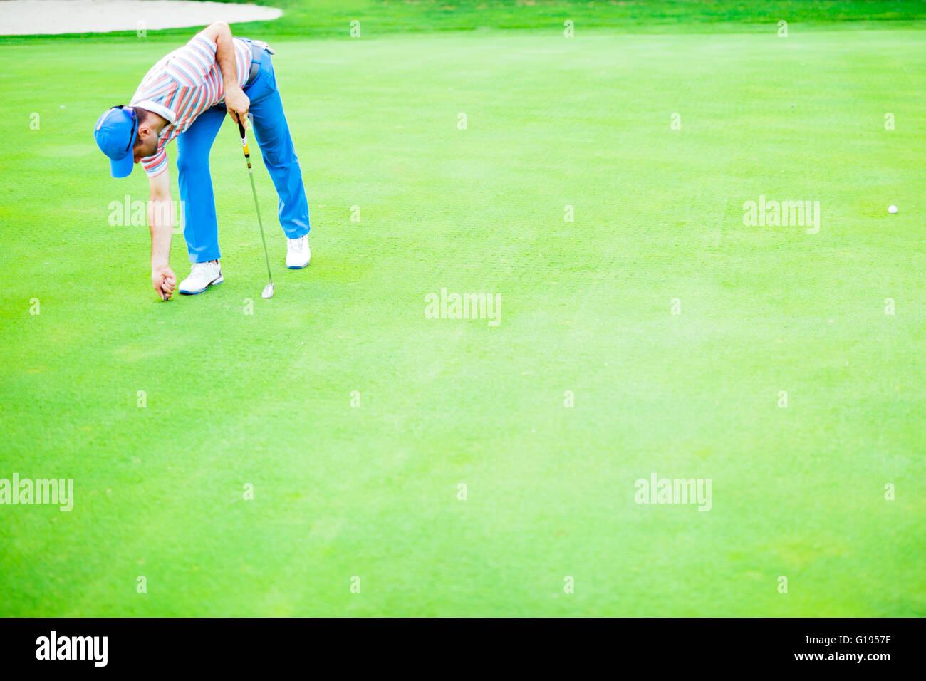 Golfspieler, die Reparatur Divot auf einer grünen Rasenfläche Stockbild