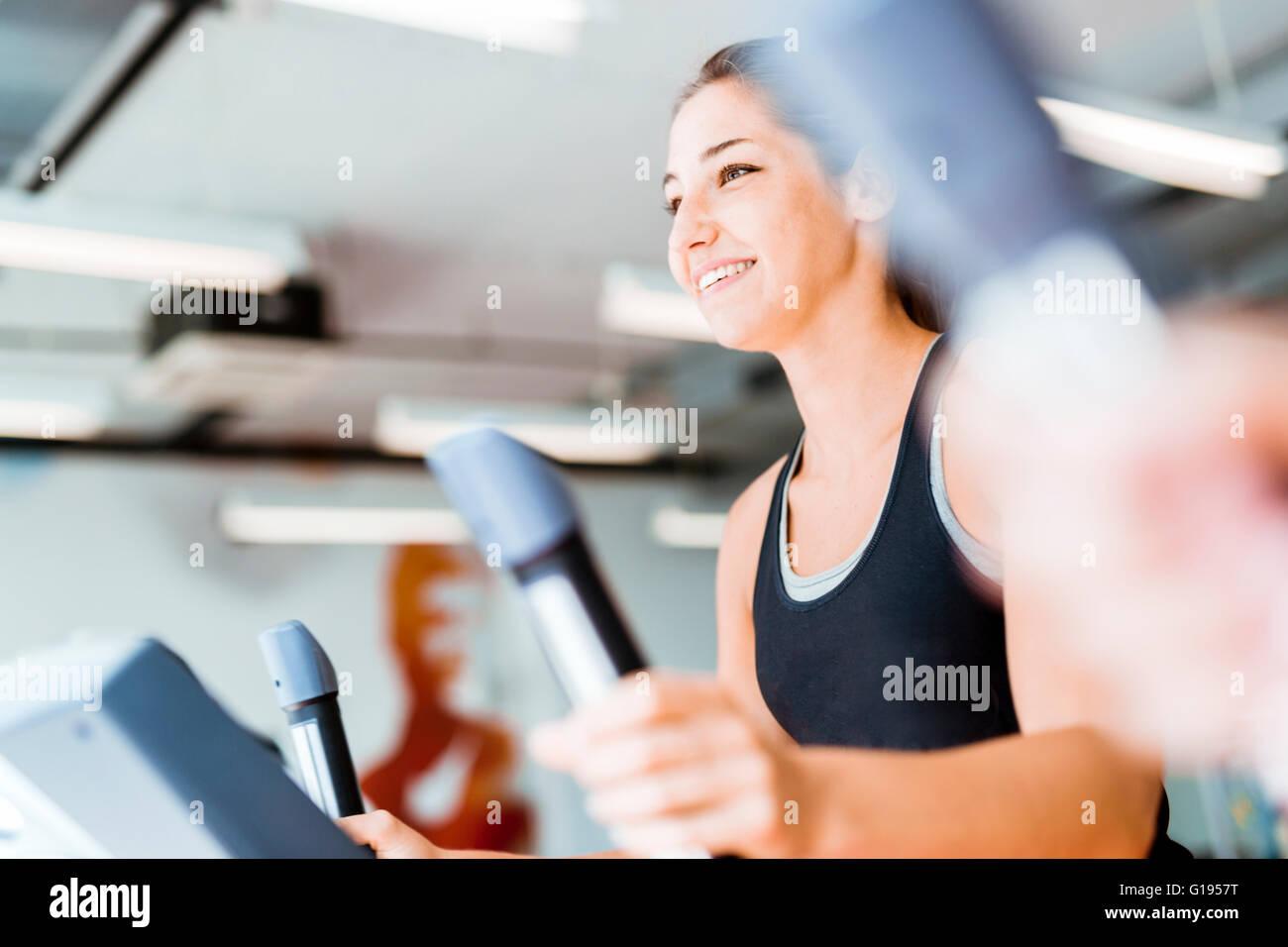 Schöne junge Dame mit dem elliptischen Trainer in einem Fitnessstudio in eine positive Stimmung Stockbild