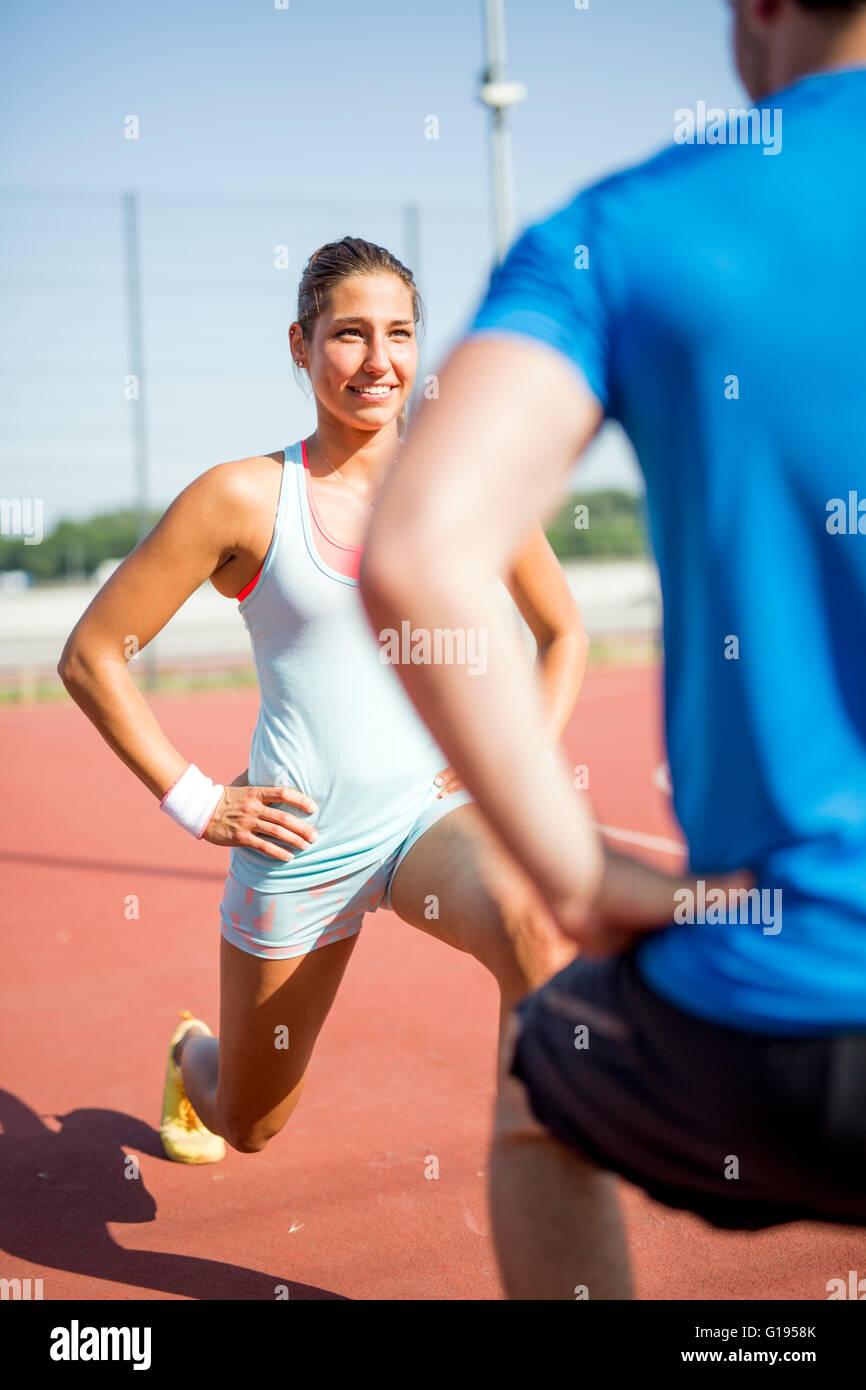 Junger sportlicher Mann und Frau dehnen im Freien an einem heißen Sommertag einander zugewandt Stockfoto