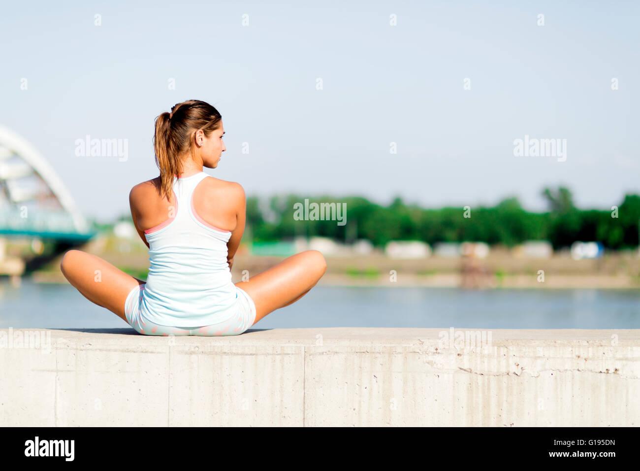 Junge Frau dehnen und entspannen in der Stadt vor dem Training Stockbild