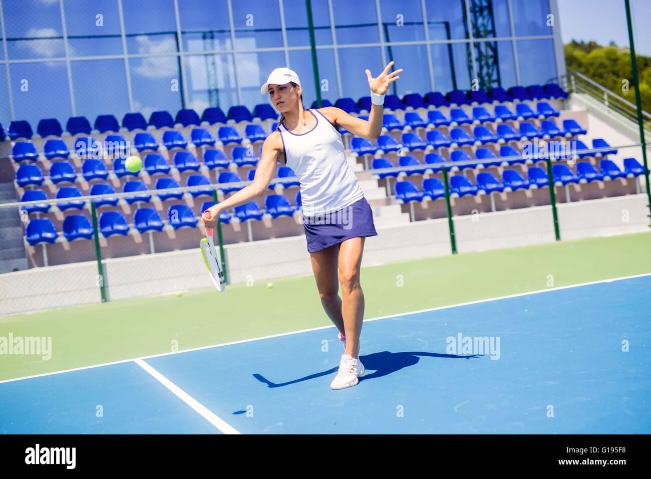 Schöne weibliche Tennisspieler in Aktion, schlagen eine Vorhand Stockbild