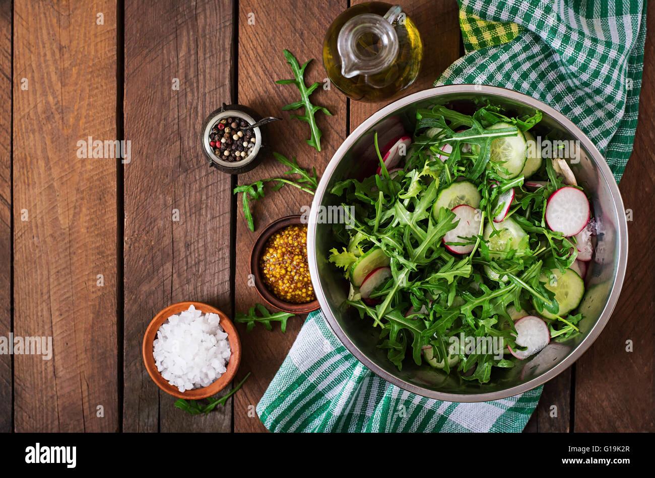 Zutaten für Salat Rucola, Radieschen, Gurken und Gewürzen. Ansicht von oben Stockbild