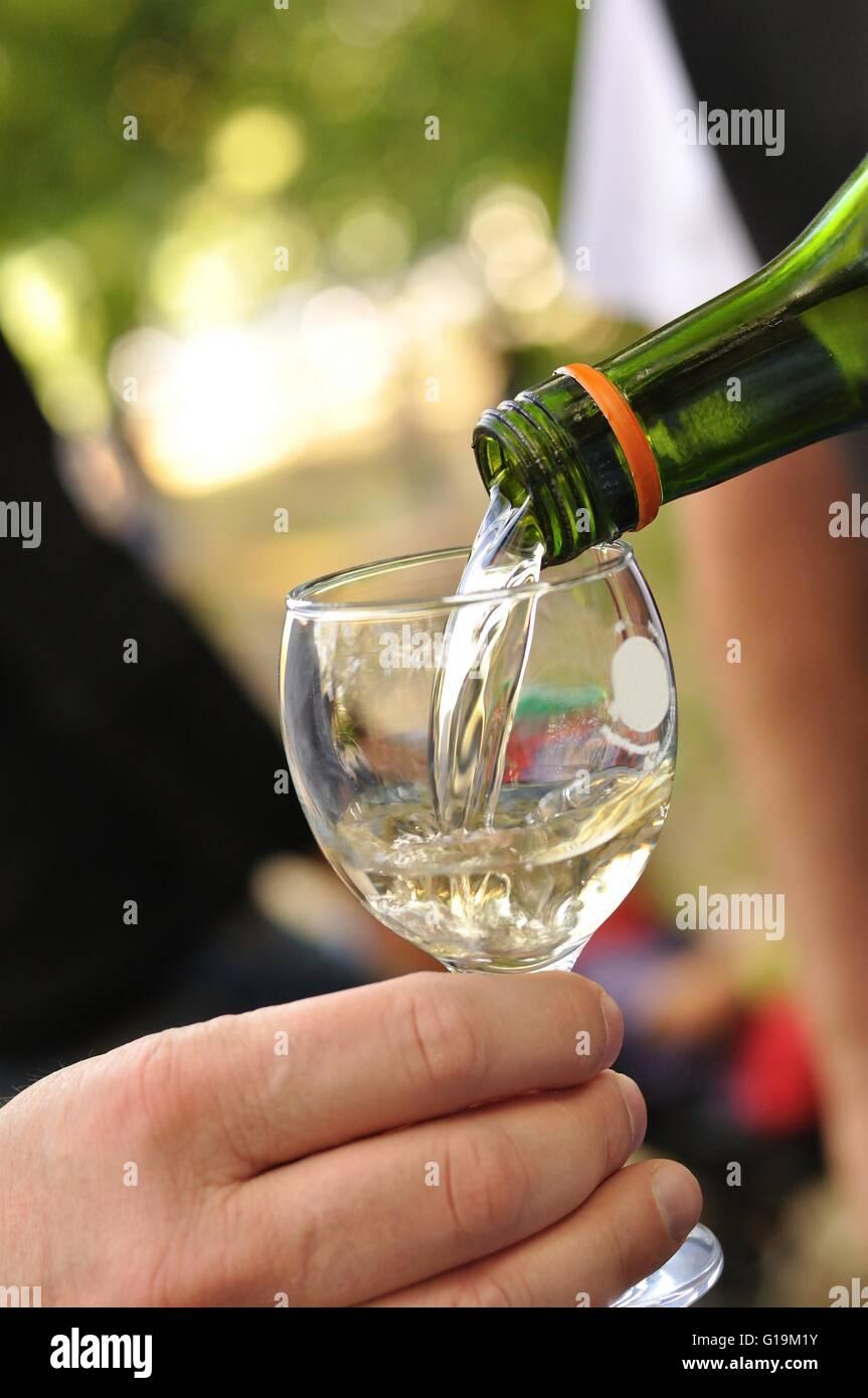 Man gießt in ein Glas Weißwein Stockbild