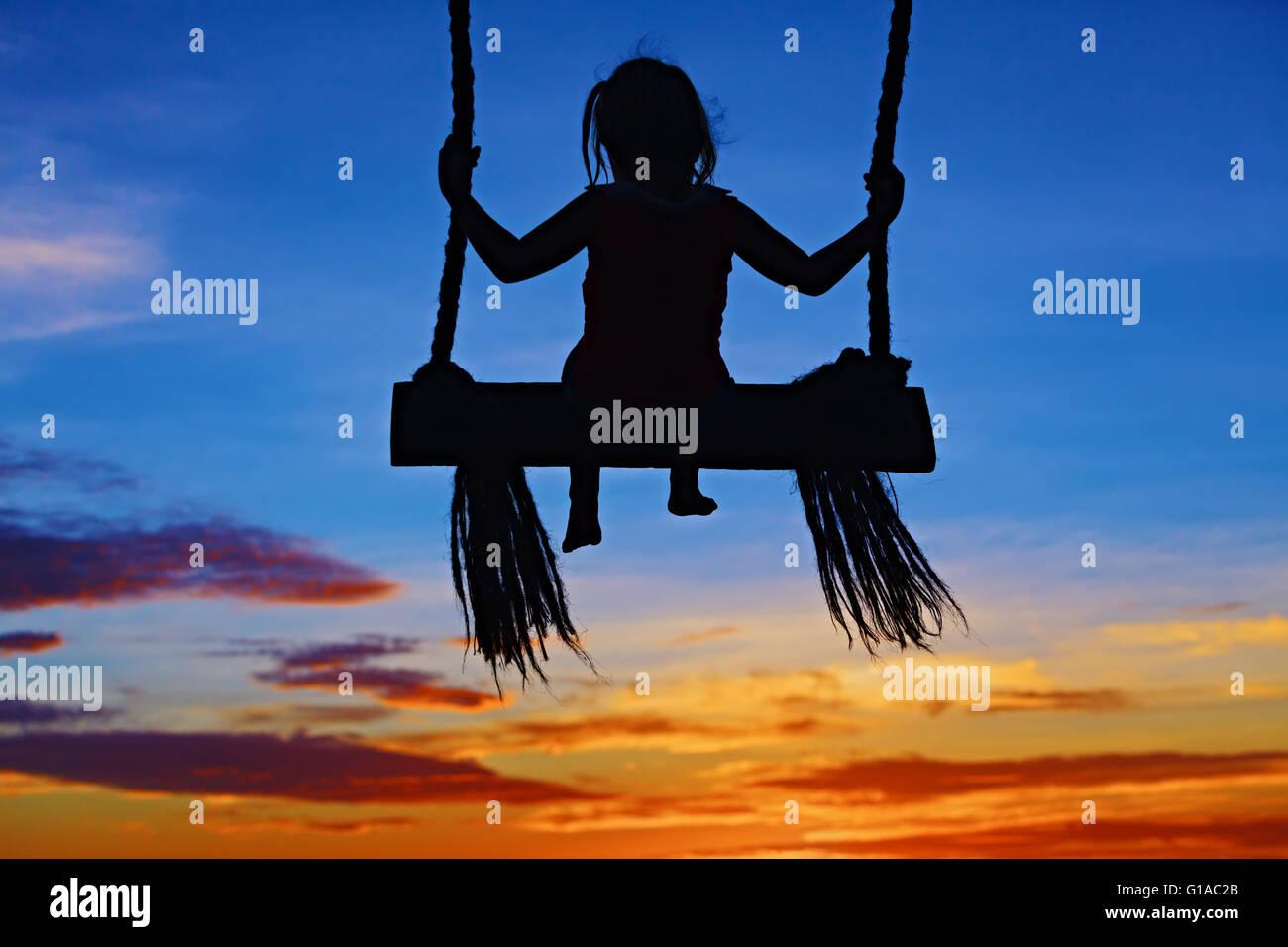 Schwarze Silhouette von Babymädchen fliegen hoch mit Spaß am Seil Schaukel auf blau orange sunset Himmelshintergrund. Stockbild