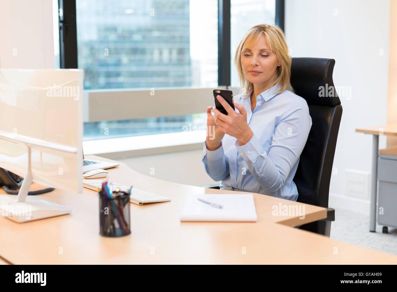 Applying Geschaftsfrau Die Im Buro Arbeiten Mittels Smartphone