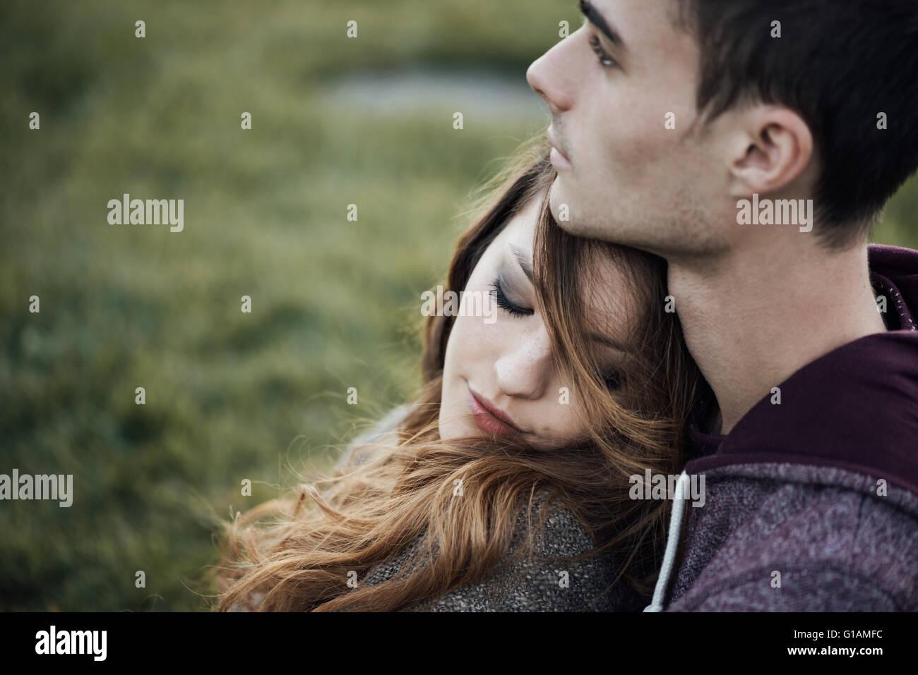 Junge liebende Paar entspannen auf dem Rasen und umarmt, sie lächelt und stützte sich auf seine Schulter, Stockbild