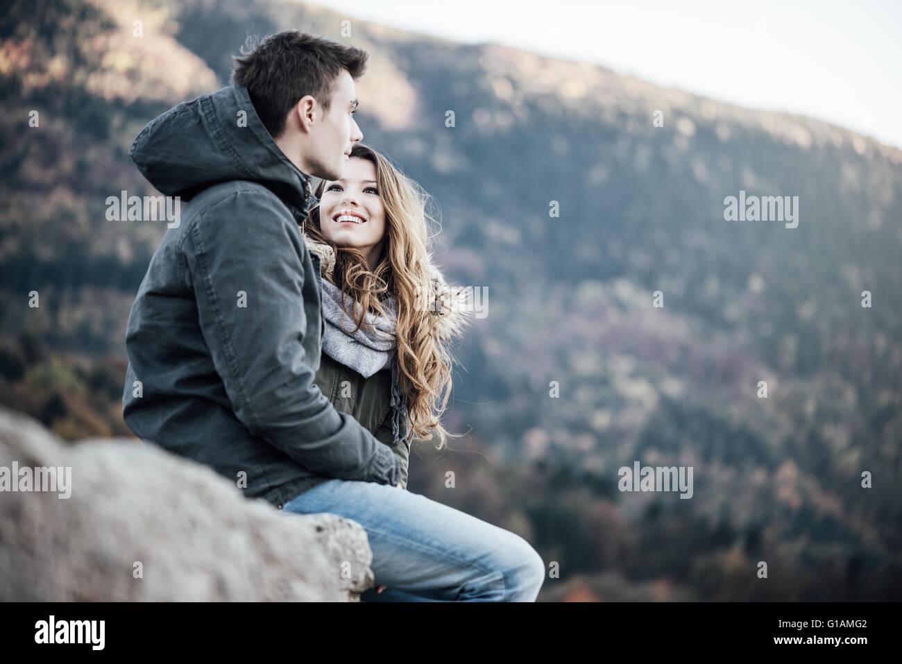 Romantische junges Paar im Winter aus, sie sitzen zusammen, sie sucht bei ihrem Freund Stockbild