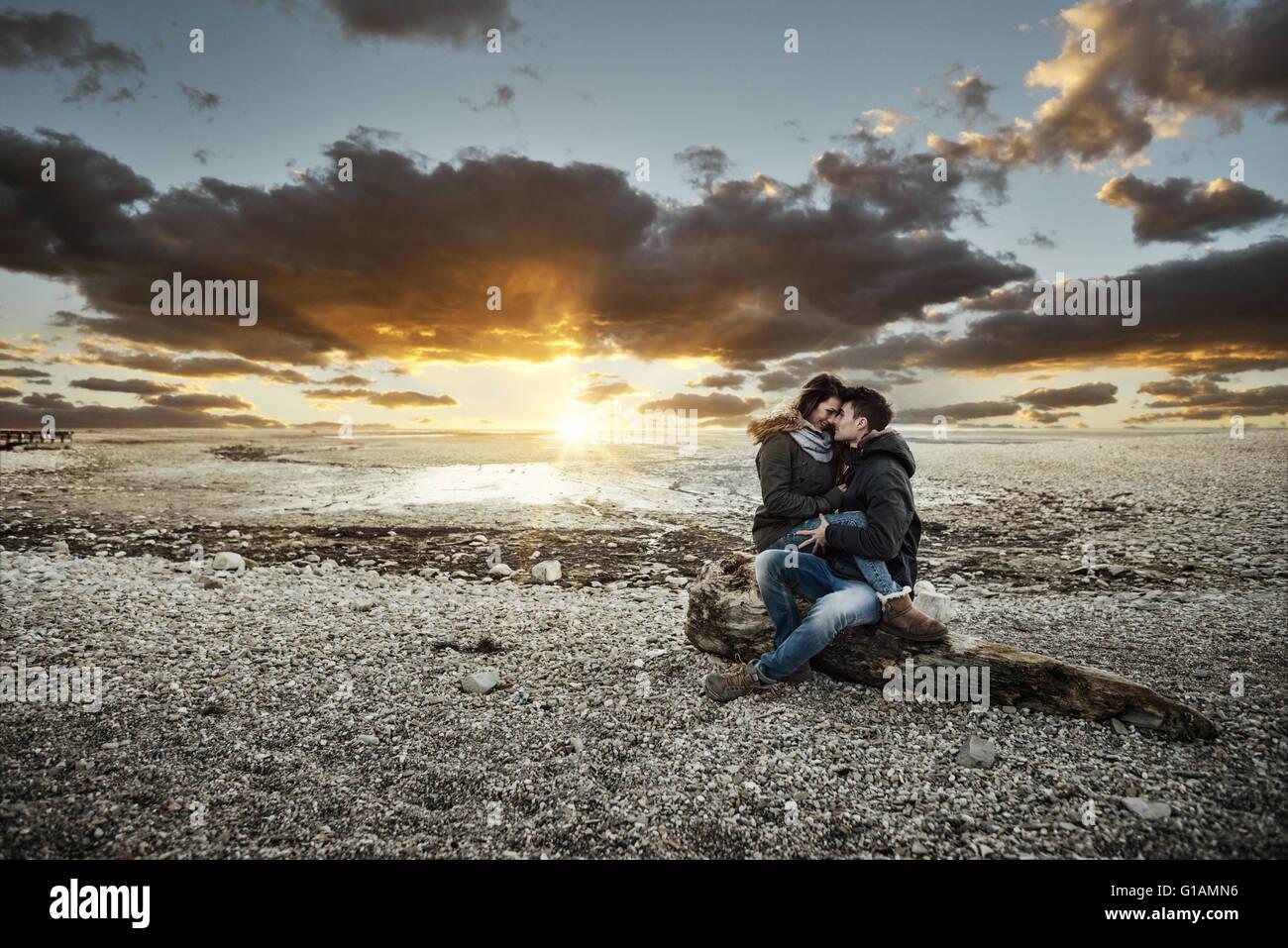 Junges Paar mit einem romantischen Date am See, sie umarmen und sitzen auf einem Baumstamm auf dem Strand, Liebe Stockbild