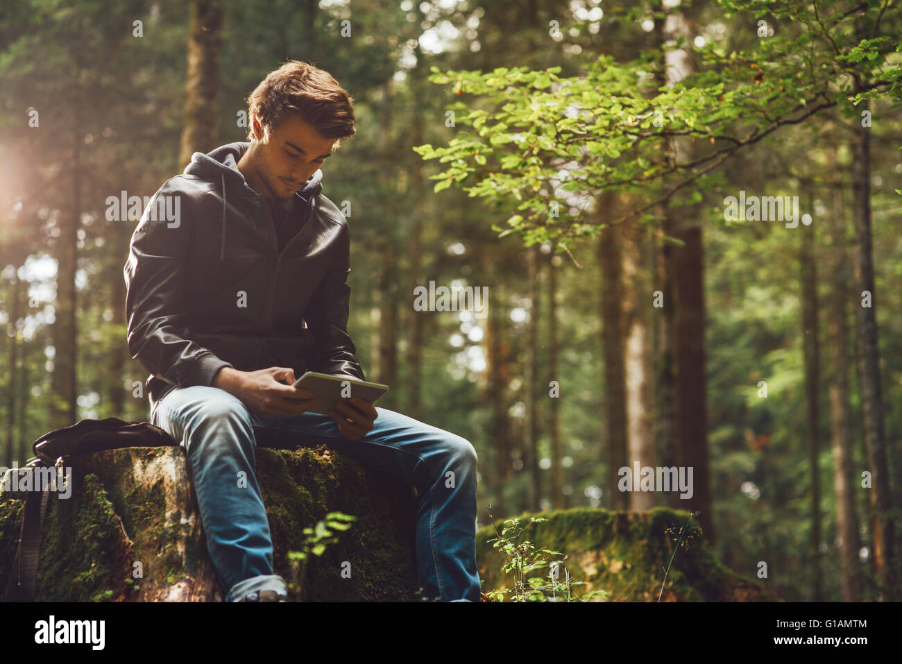 Hübscher Jüngling sitzt im Wald und unter Verwendung eines digitalen Touch-Screen-Tablette, wi-Fi-Verbindung und Stockfoto