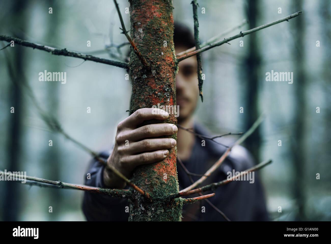 Junger Mann versteckt in den Wäldern und halten den Stamm, die hand auf Vordergrund, selektiven Fokus Stockbild