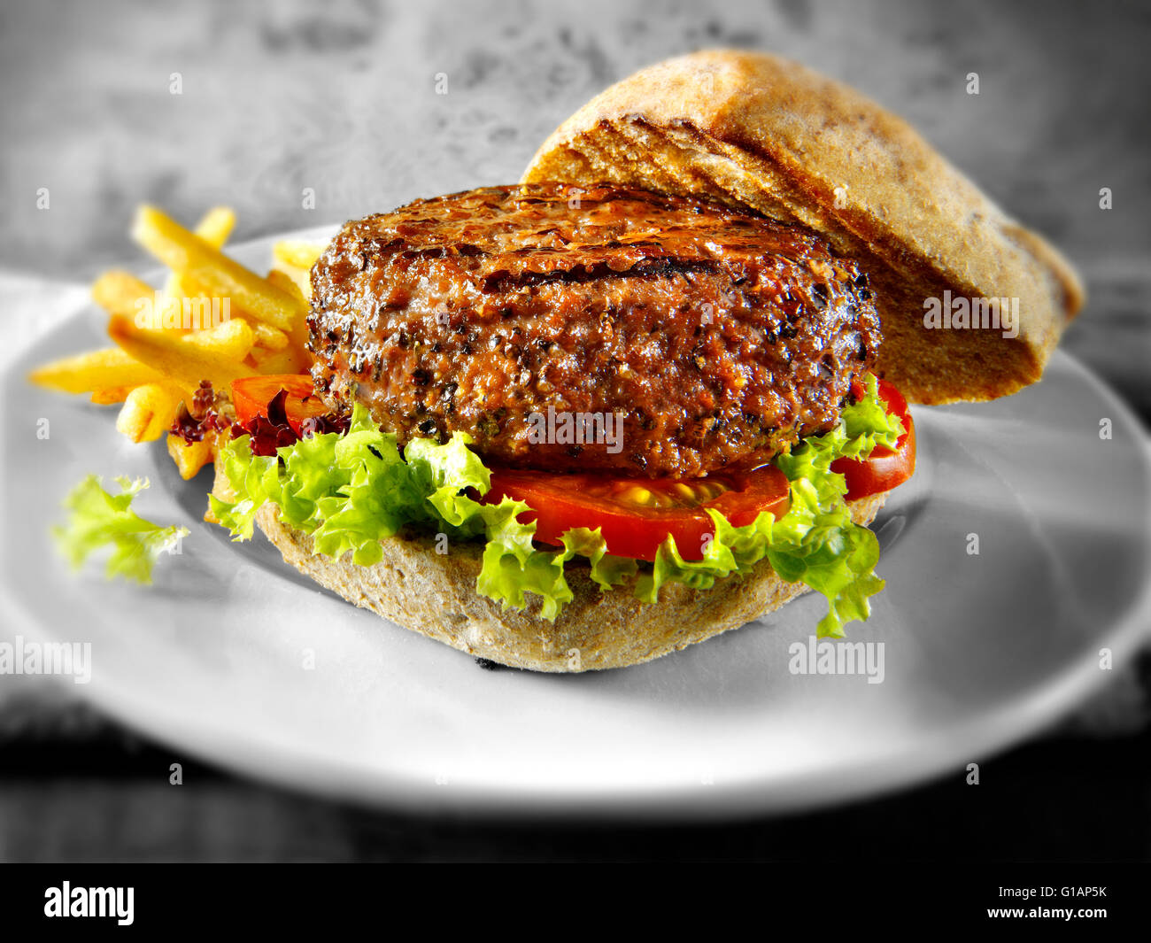 Beef-Burger oder Hamburger in einem mit Vollkorn Brötchen mit Pommes frites Stockbild