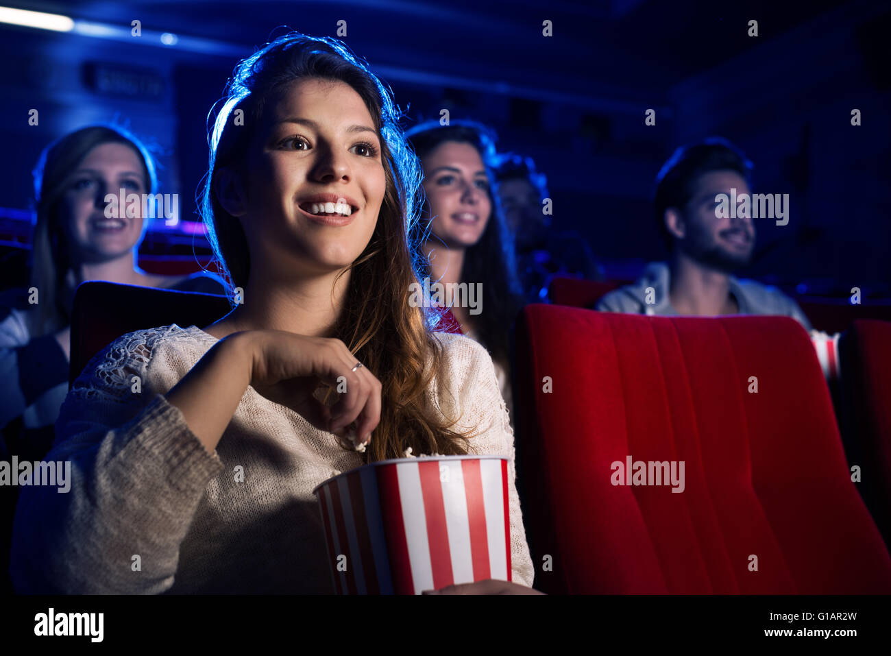 Junge lächelnde Frau einen Film im Kino und Essen Popcorn, Unterhaltung und Kino-Konzept Stockbild