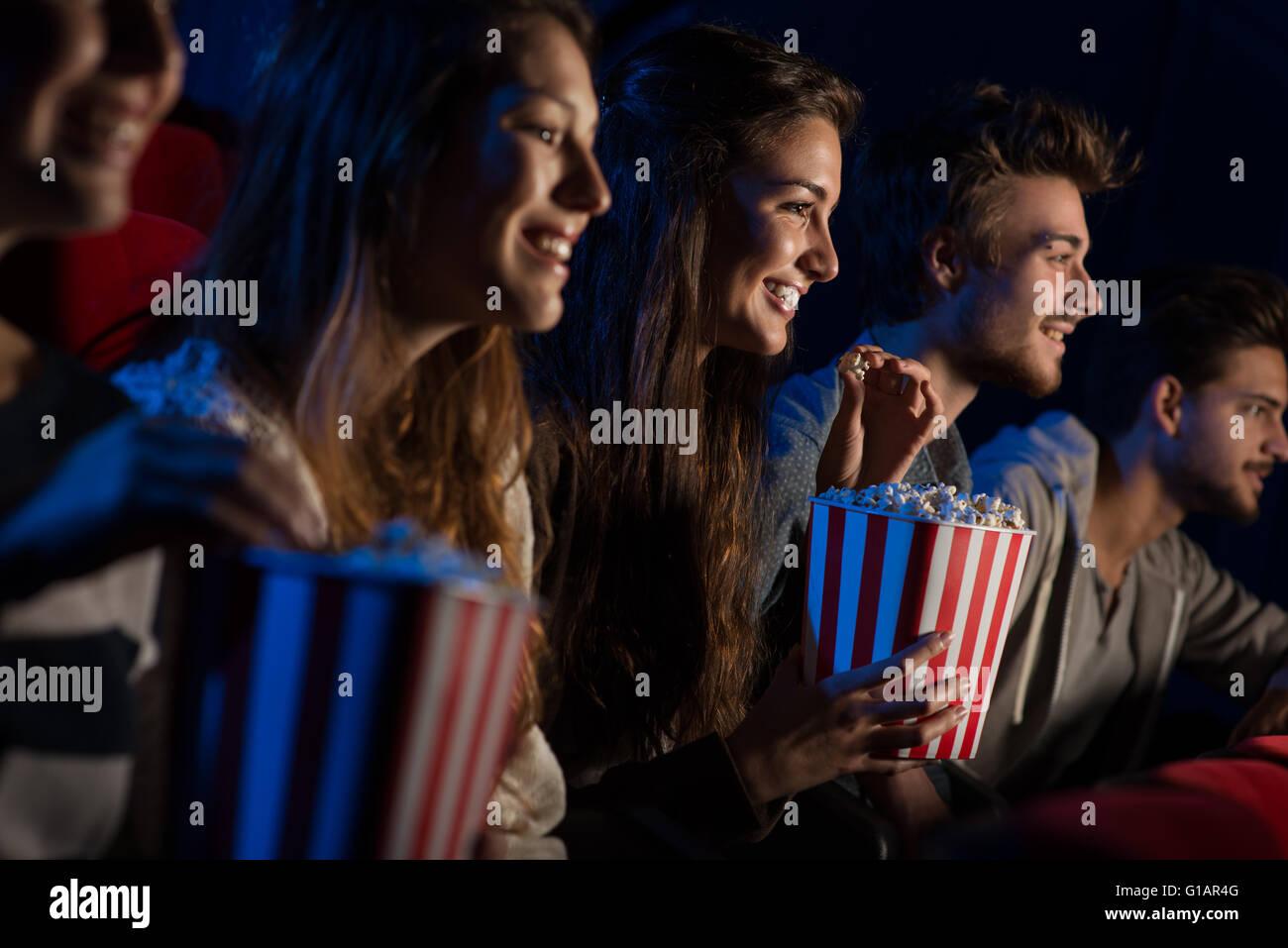 Gruppe Jugendlicher Freunde im Kino einen Film zusammen und Essen Popcorn, Unterhaltung und Genuss-Konzept Stockbild