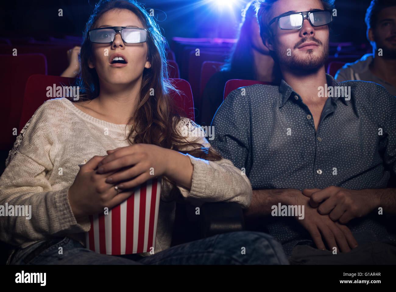 Junge Teenager im Kino eine Brille und einen 3d Film, ist eine Mädchen essen Popcorn, Unterhaltung und Filmen Stockbild