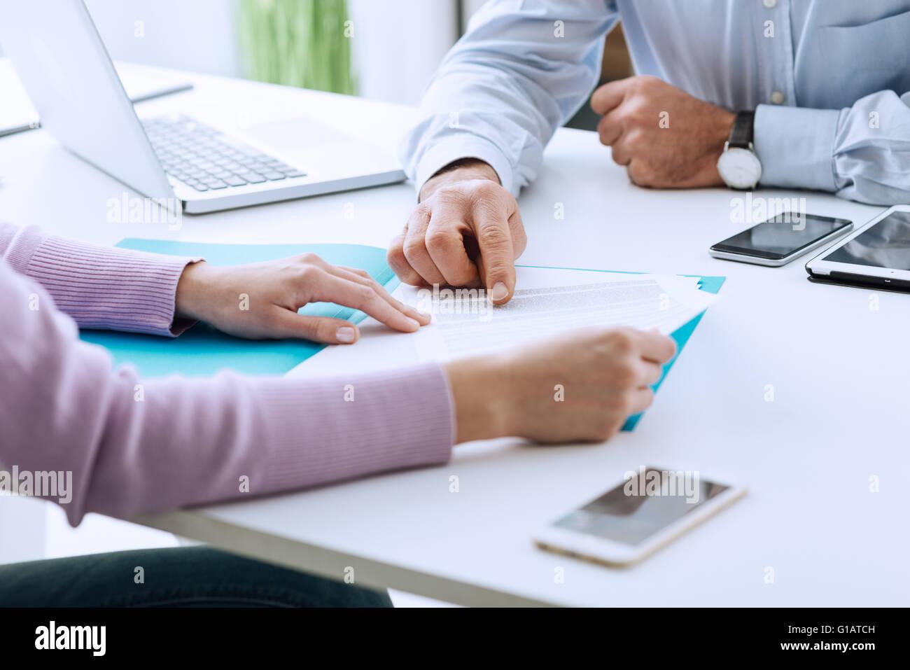 Junge Frau mit einem Geschäft treffen mit Führungskraft in seinem Büro, er zeigt auf einen Vertrag Stockbild