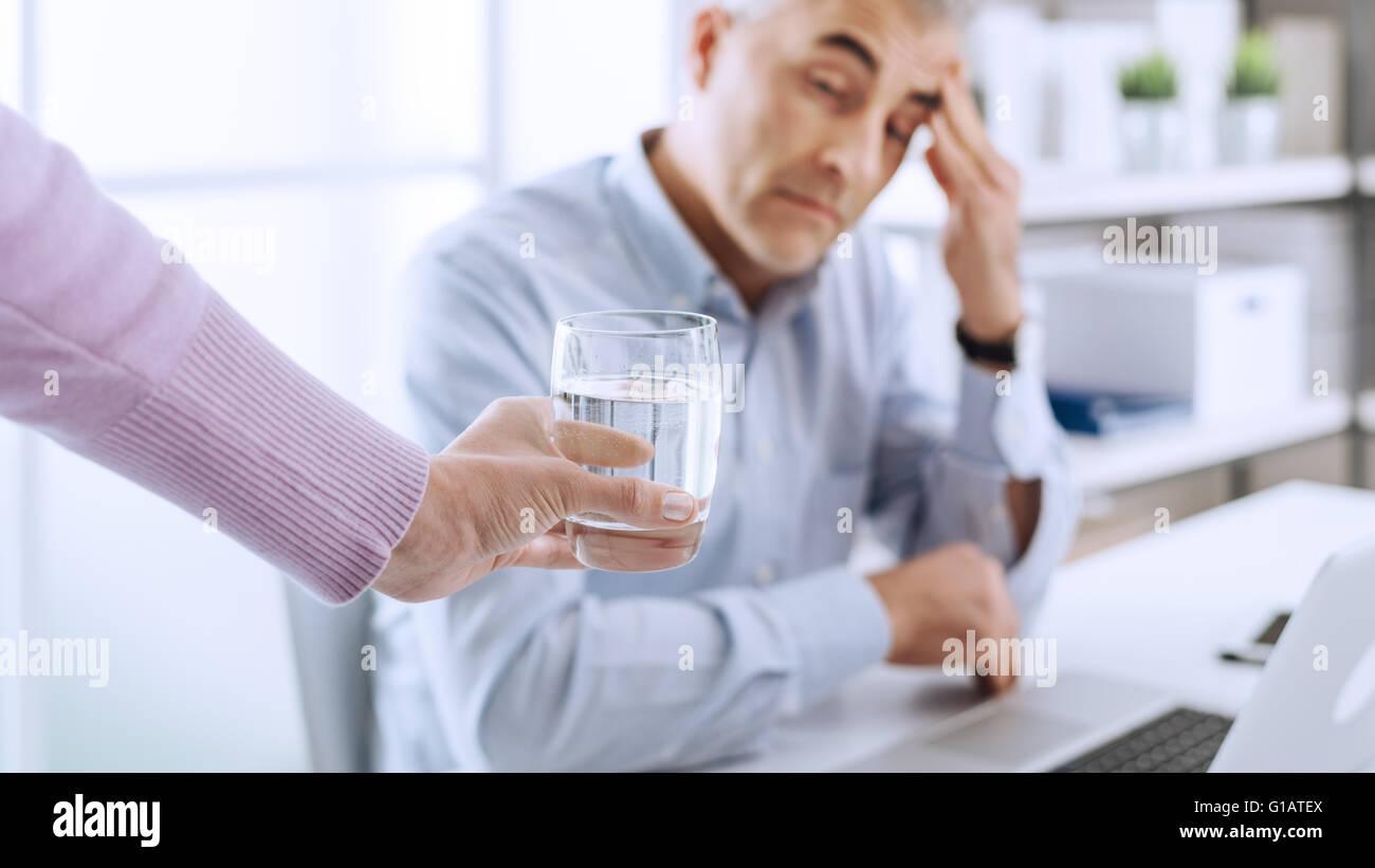 Müde Geschäftsmann im Büro am Schreibtisch arbeiten und haben eine starke Kopfschmerzen, sein Kollege Stockbild