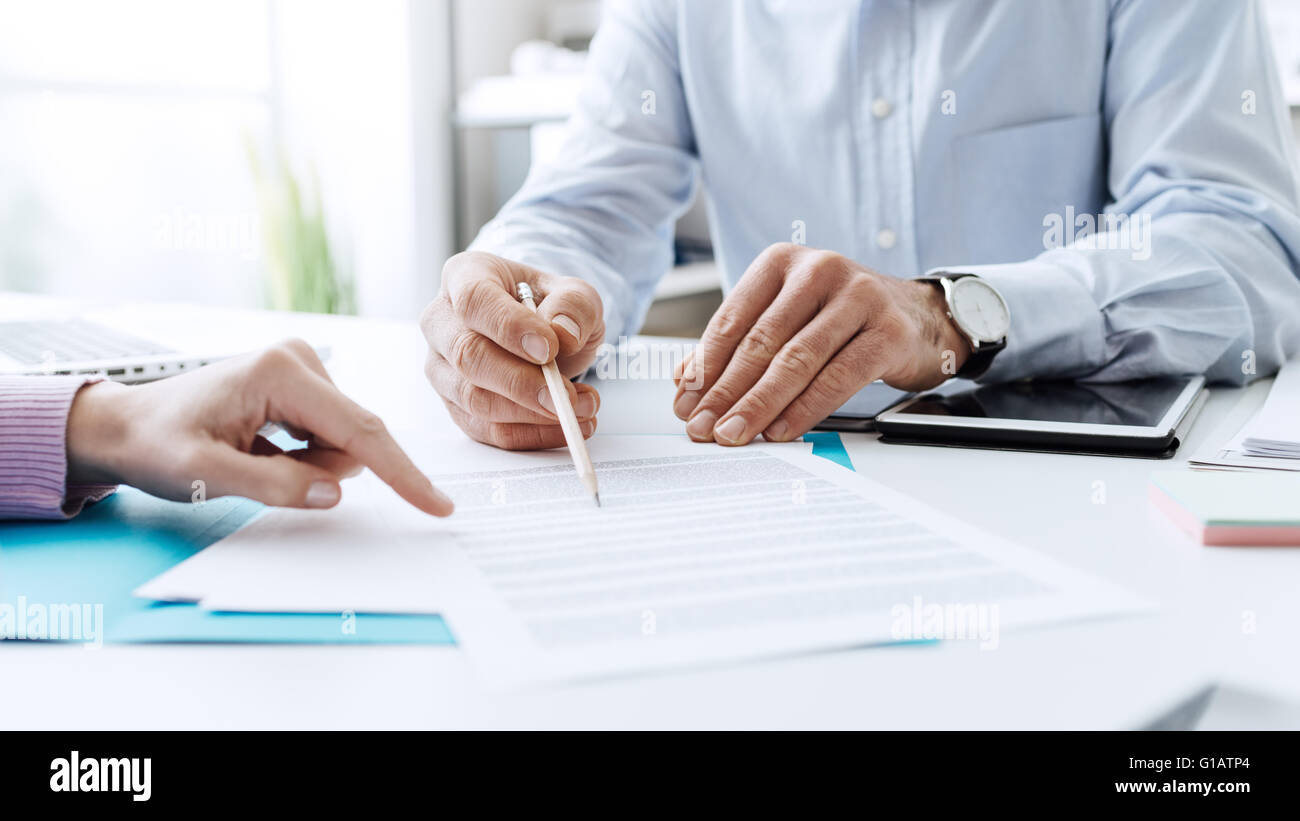 Geschäftsleute, Vertragsverhandlungen, sie verweist auf ein Dokument und gemeinsam zu diskutieren Stockbild