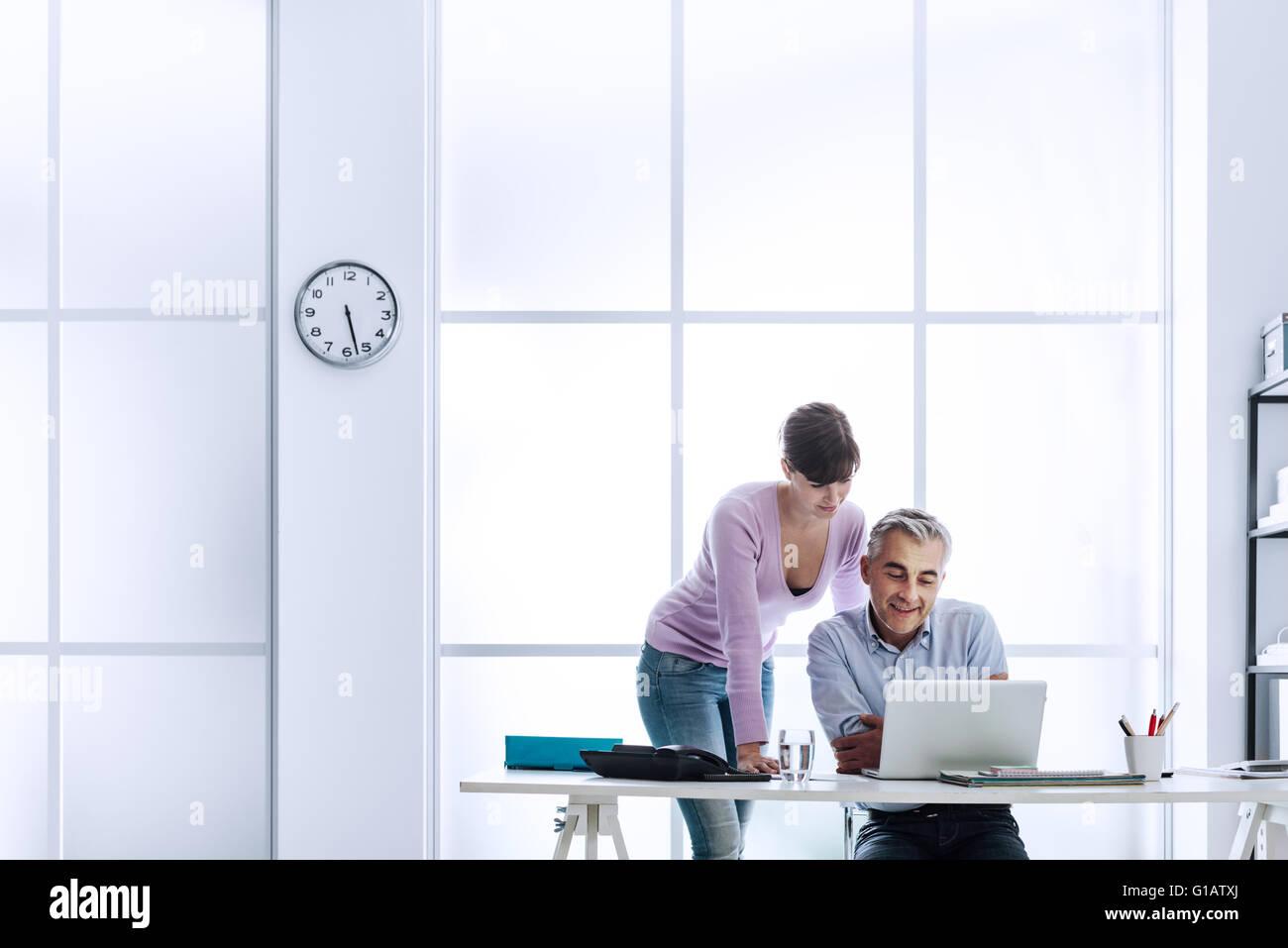 Executive mit seiner Assistentin am Schreibtisch arbeiten, sie sind benutze ein Laptop und Internetverbindung Stockbild