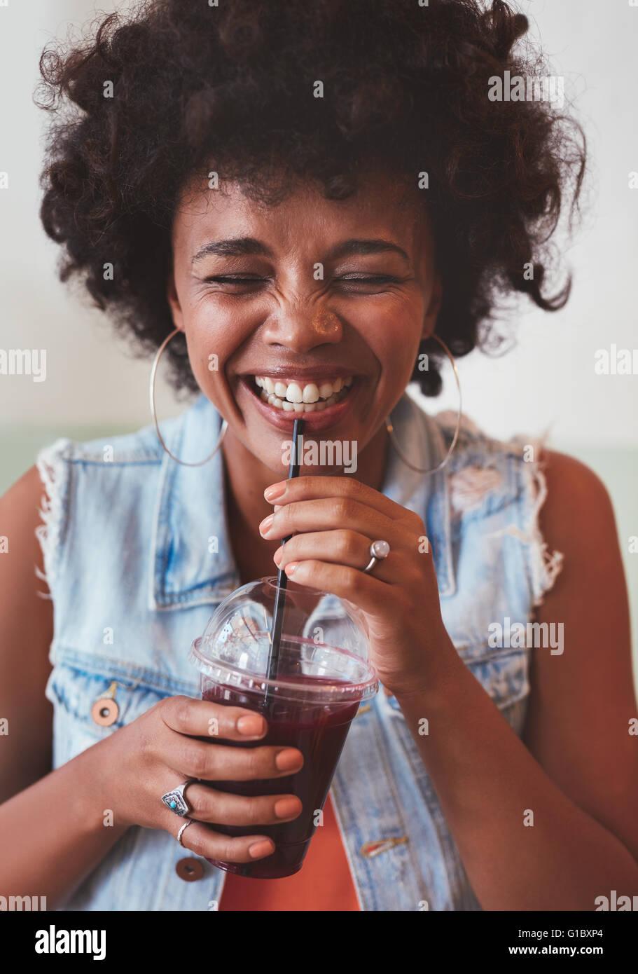 Porträt der fröhliche junge Frau trinken Saft aus frischen Früchten und lächelnd hautnah. Glückliche Stockbild