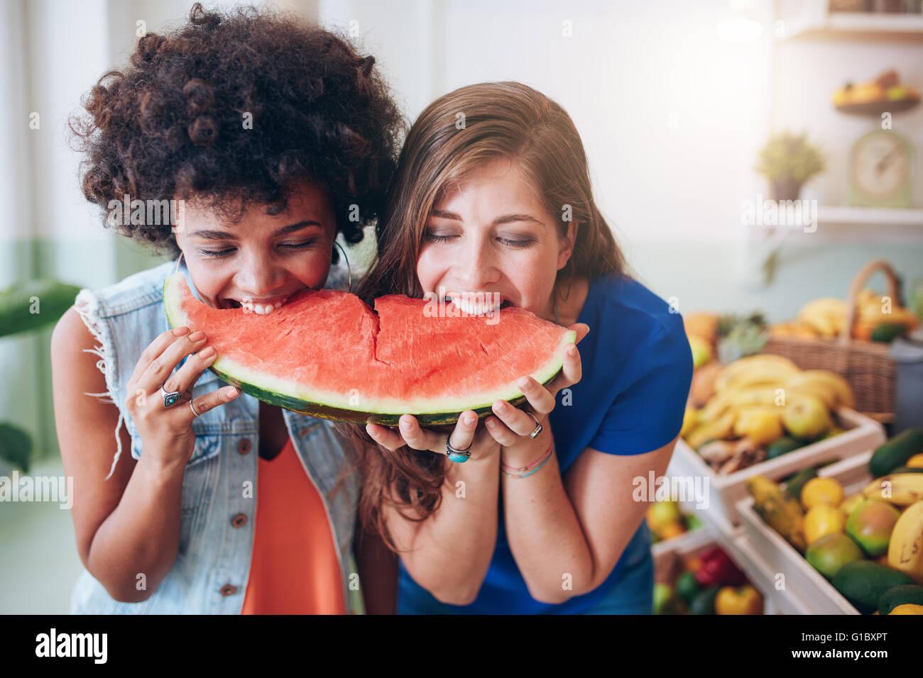 Zwei junge Frau Wassermelone essen und Spaß haben. Gemischte Rassen Freundinnen zusammen Essen ein Stück Stockbild