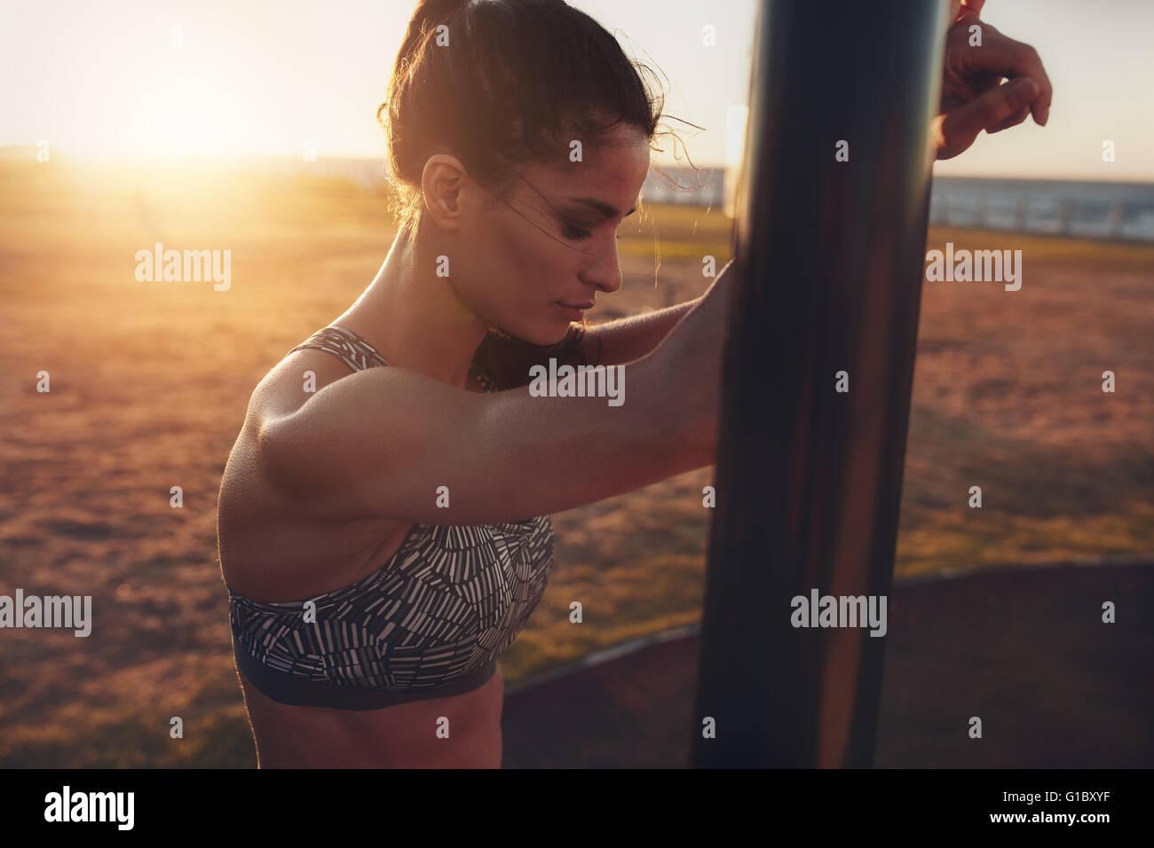 Schuss von Fit junge Frau am Strand bei Sonnenuntergang hautnah. Sportlerin gelehnt, um Ausrüstung am Strand Stockbild