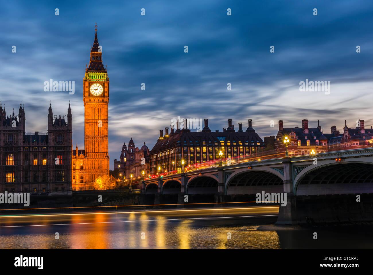 Langzeitbelichtung in der Abenddämmerung von Bussen auf Westminster Bridge und Boote auf der Themse, London, UK. Stockfoto
