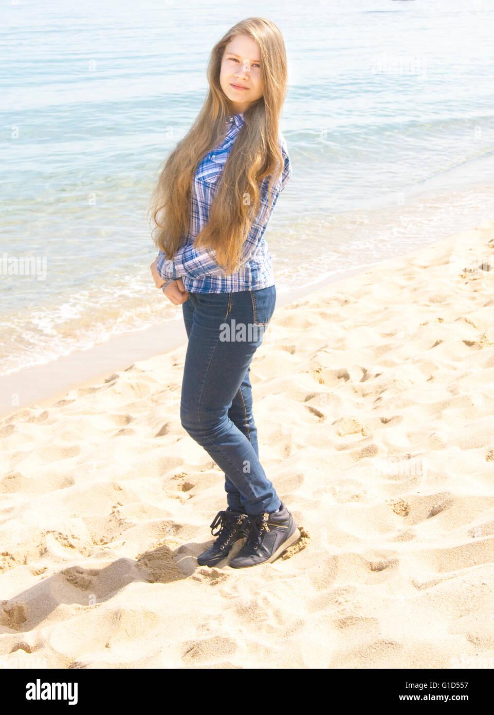 e686d926f8f667 Junge schöne Mädchen, europäischen, lange braune Haare, sechzehn Jahre in  Jeans und Rock steht, am Sandstrand in der Nähe von Meer.
