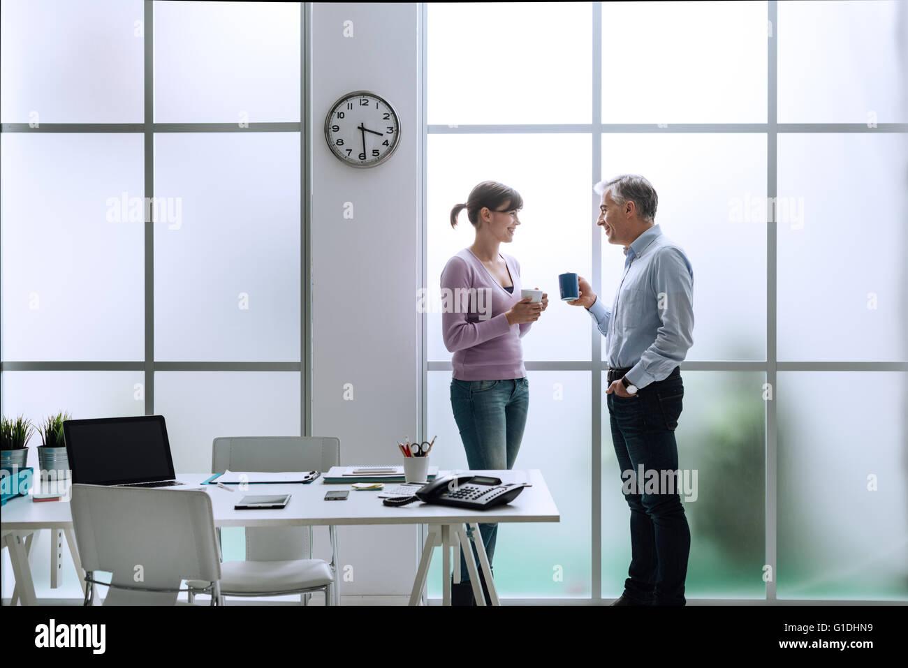 Fröhliche Büroangestellte im Büro, entspannen, mit einer Kaffeepause und Chat zusammen, sie stehen Stockbild