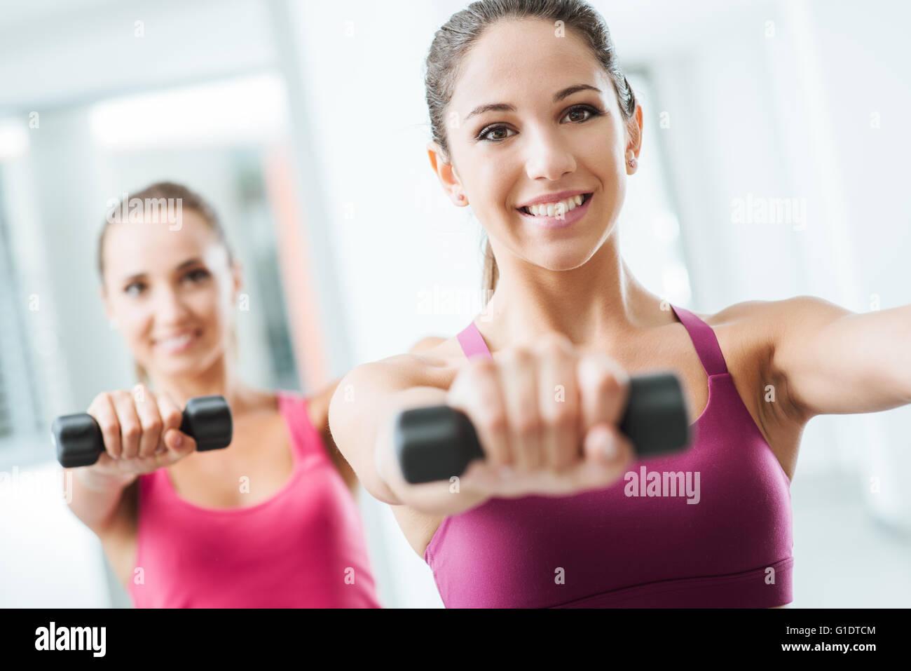 Sportliche Teenagermädchen im Fitness-Studio trainieren und Gewichtheben mit Hanteln, Körperpflege und Stockbild